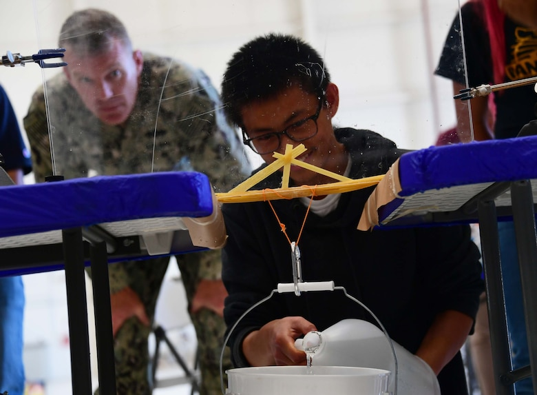 A student stares at a handmade bridge of spaghetti during the contest.
