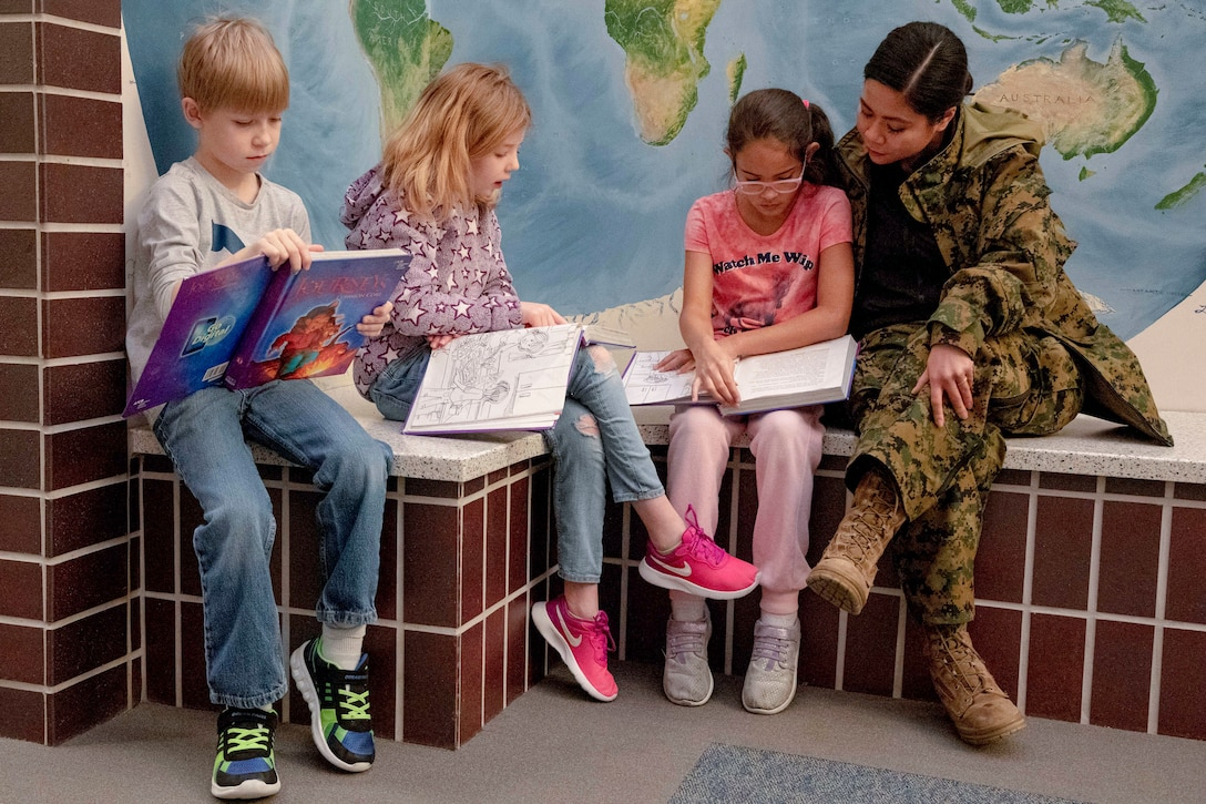 A sailor and three kids sit in front of a map and read books.