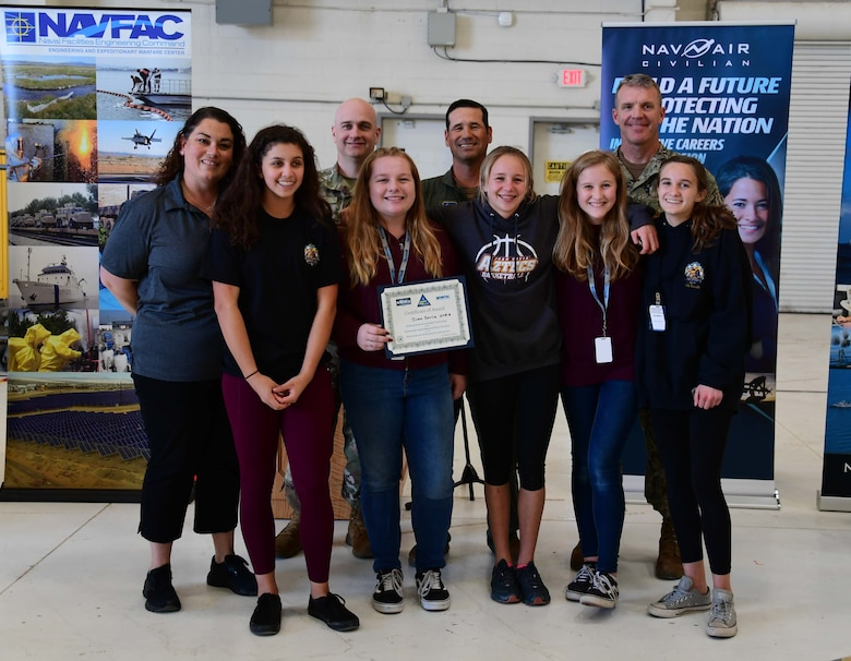 Col. keith Ward stands for an award photo with the winning students.