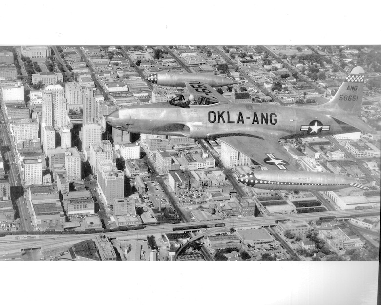 Black and white aerial photo of F-80 Shooting Star flying over a city.