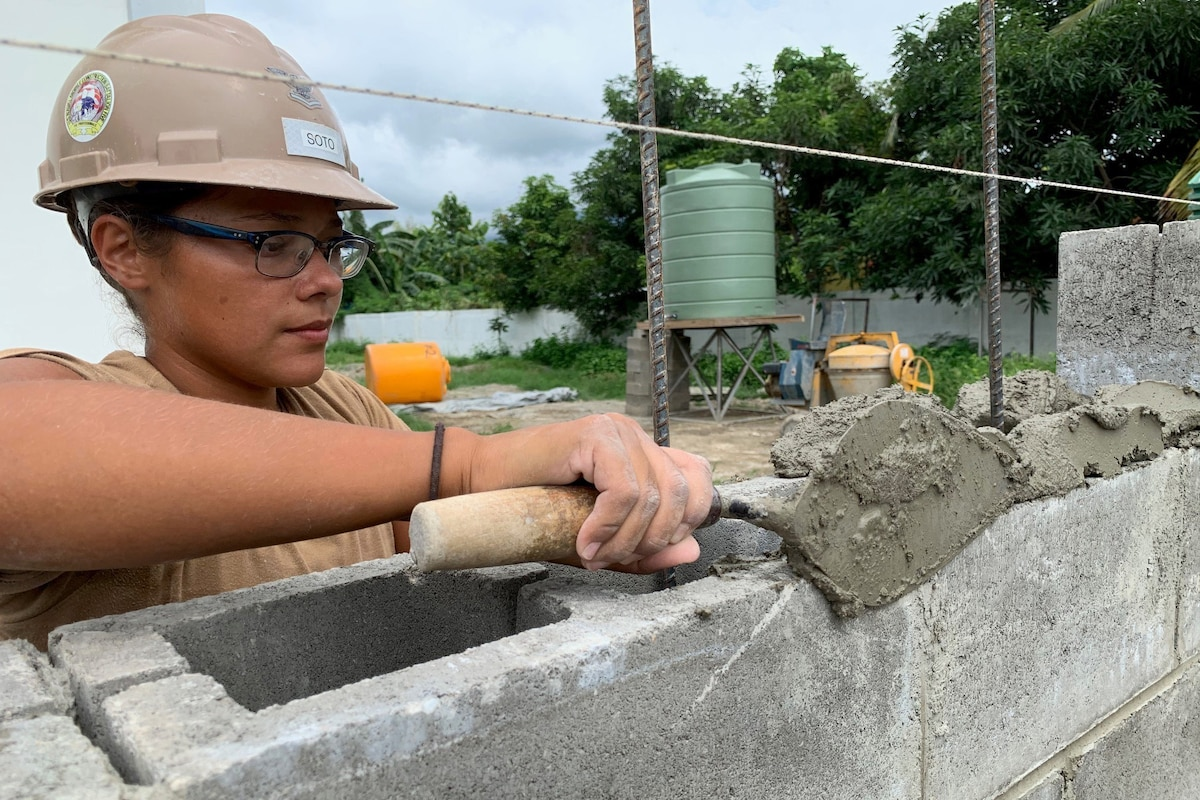 A Navy Seabee uses a trowel to spread mortar on concrete blocks.