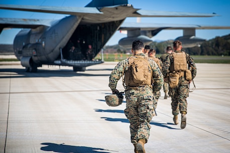Marines running toward a KC-130J Hercules