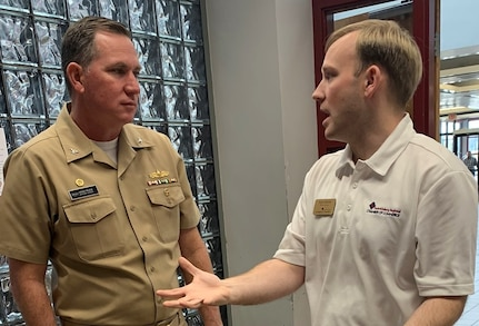 """IMAGE: SPOTSYLVANIA, Va. (Feb. 29, 2020) – Capt. Casey Plew, Naval Surface Warfare Center Dahlgren Division (NSWCDD) commanding officer, speaks with Kyle Allwine, director of government affairs for the Fredericksburg Regional Chamber of Commerce, at the annual science, technology, engineering, mathematics (STEM) Summit open to the public at Chancellor High School. """"Participating in STEM education is a valuable investment in both your future as well as society's future,"""" Plew told students in his keynote speech. """"Soak up the awesomeness of all of the different STEM efforts displayed for you. And get excited. One day, someone could be telling a future group of students about something amazing you developed – and it all started with you getting engaged in STEM at school."""""""