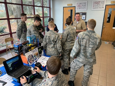 """IMAGE: SPOTSYLVANIA, Va. (Feb. 29, 2020) – Capt. Casey Plew, Naval Surface Warfare Center Dahlgren Division (NSWCDD) commanding officer, speaks with students who are cadets in the Virginia Wing Civil Air Patrol at the annual science, technology, engineering, mathematics (STEM) Summit open to the public at Chancellor High School. Plew was among the NSWCDD leaders, scientists and engineers who joined a myriad of organizations to engage students with science, technology, engineering, mathematics (STEM) demonstrations. """"For Patriots ages 12 and up, Civil Air Patrol is a vital force that protects Americans in need by responding to disaster, preserves the values that make our country great by developing young leaders and ensures our country's preeminence in Aerospace and Cyberspace Education,"""" states the organization's website."""