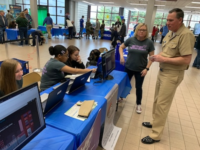 """IMAGE: SPOTSYLVANIA, Va. (Feb. 29, 2020) – Capt. Casey Plew, Naval Surface Warfare Center Dahlgren Division (NSWCDD) commanding officer, talks with  members of the Spotsylvania High School's Girls Go CyberStart group at the annual science, technology, engineering, mathematics (STEM) Summit hosted by Chancellor High School. Plew was among the NSWCDD leaders, scientists and engineers who joined a myriad of organizations to engage students with science, technology, engineering, mathematics (STEM) demonstrations. """"By the end of Girls Go CyberStart, students will have delved into disciplines such as cryptography, digital forensics and open source intelligence gathering and more,"""" according to the organization's website. """"The program gets increasingly difficult, but the first stage is designed to be accessible to anyone to uncover hidden superstars with natural ability.""""  (U.S. Navy photo/Released)"""