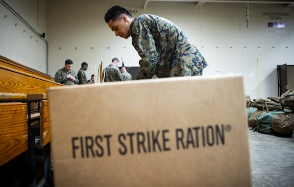 Marine stands next to meal ration box.