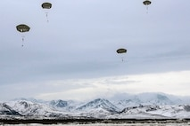 Parachutists drop down onto a snowy landscape with mountains in the background.