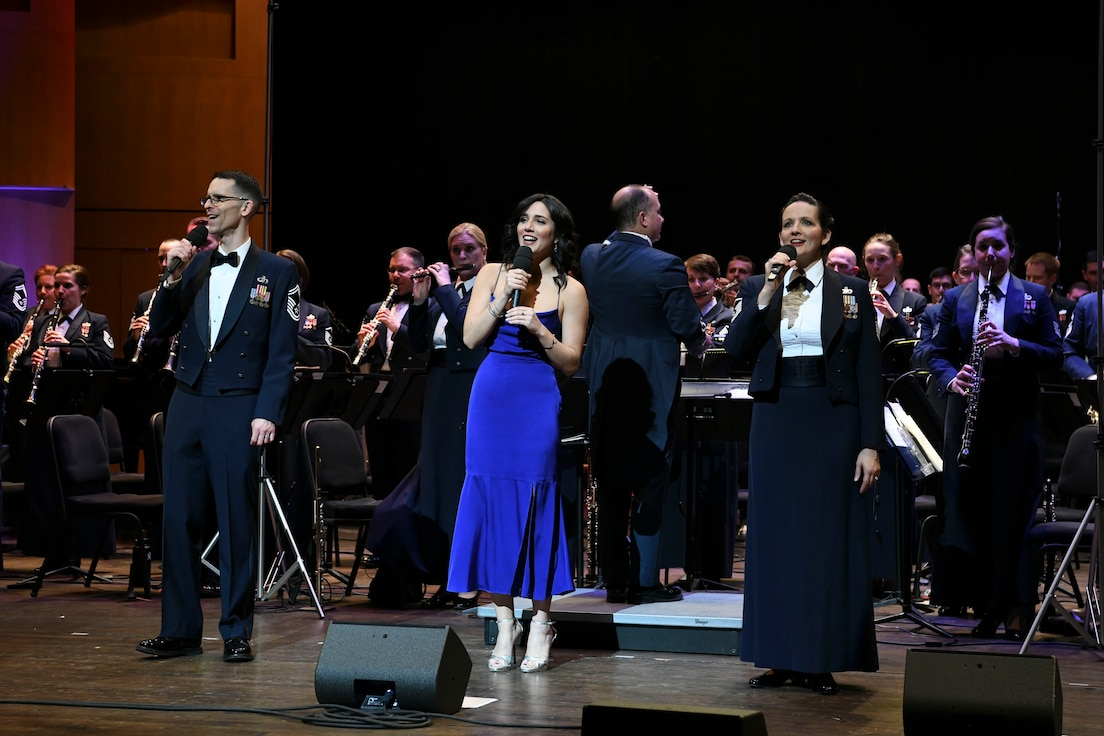 """Senior Master Sgt. Matthew Irish, superintendent of outreach for The U.S. Air Force Band, Samantha Massell, singer, and Master Sgt. Emily Wellington, Singing Sergeants alto vocalist sing together during the band's Guest Concert Series at the Rachel M. Schlesinger Concert Hall and Arts Center in Alexandria, Va., Feb. 20, 2020. The concert featured a lineup of more than 10 songs including pieces from """"The Sound of Music"""" and Walt Disney's """"Pocahontas"""". (U.S. Air Force photo by Airman 1st Class Spencer Slocum)"""