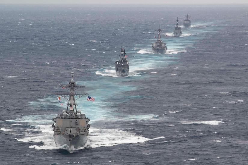 Five warships sail in formation in the ocean.