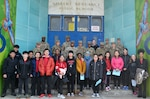 A group of students and active duty military members pose in front of Gilbert Spruance School in Philadelphia on Read Across America Day.