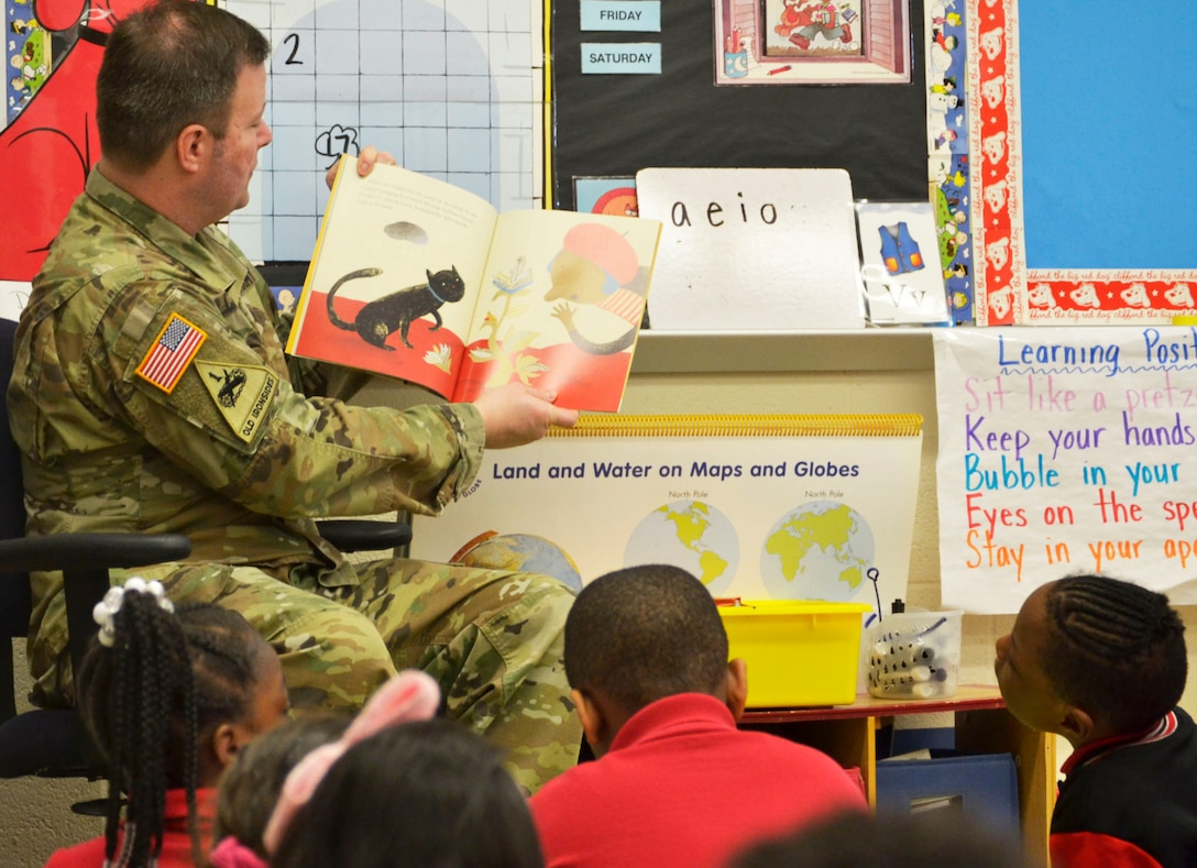 A US Army Soldier reads to school children during Read Across America day.