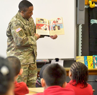 A US Army Soldier reads to school children during National Read Across America Day.