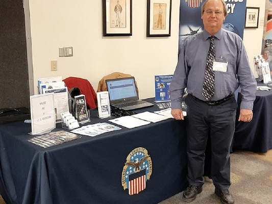 Jay Hilderbran stands ready to greet potential candidates to the DLA Land and Maritime Booth at the College of Arts and Sciences Economics Department Spring Career on February 20, 2020.