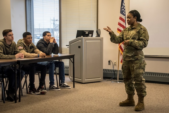 Military member stands at the front of a classroom teaching diversity