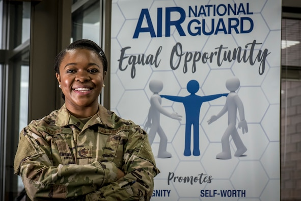 Military member poses in front of an Equal Opportunity poster