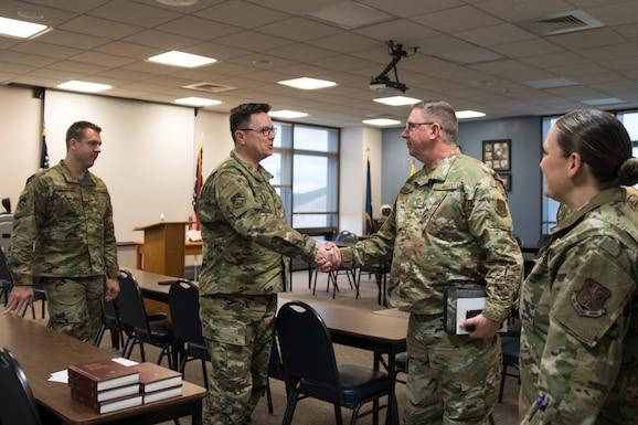 Military members shake hands before church service