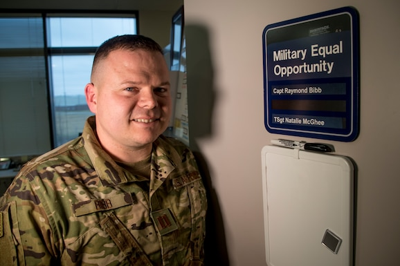 Military member poses for a photo in front of the Military Equal Opportunity office sign.