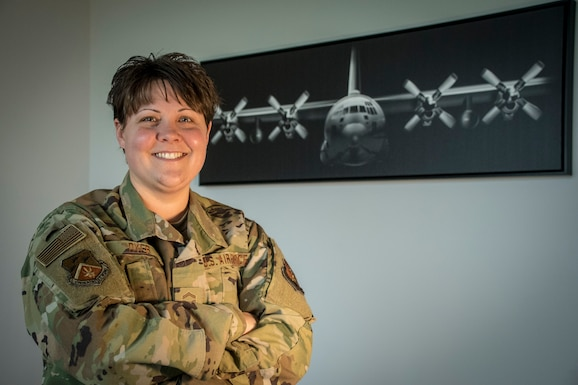 Military member poses in front of a C-130 poster.