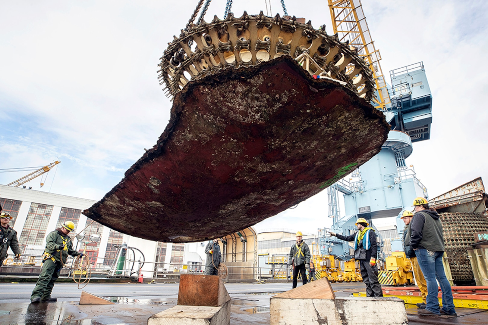Riggers watch as a crane lifts a massive piece of submarine hull onto a barge for disposal.