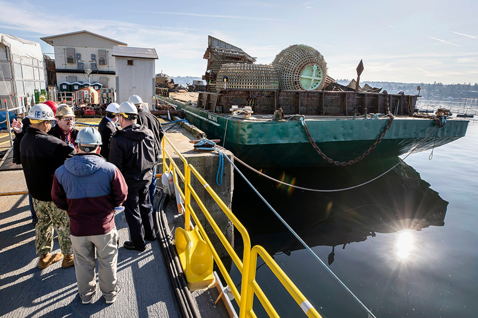 Leaders watch a barge get loaded with scrap.