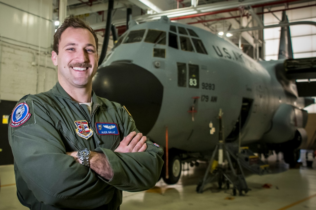 USAF Pilot poses for a photo in front of a C-130 in a maintenance hanger