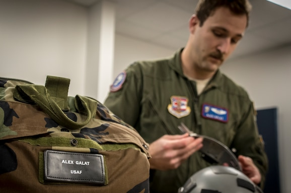 Military Pilot preps flight equipment.