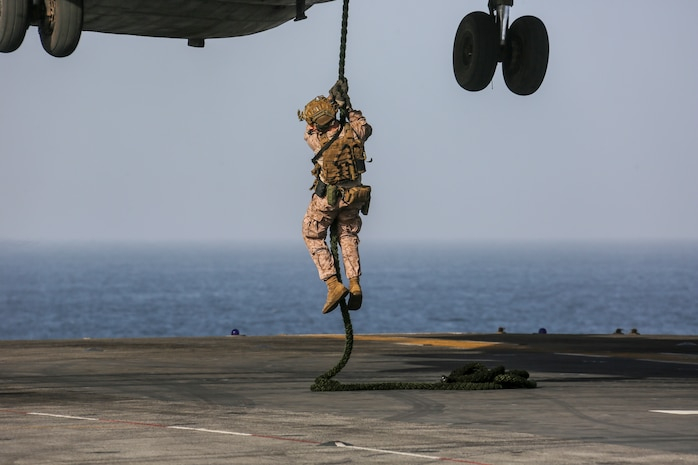 200229-M-OO419-1020 GULF OF OMAN (Feb. 29, 2020) A Marine assigned to the Maritime Raid Force, 26th Marine Expeditionary Unit (MEU), fast-ropes from a CH-53E Super Stallion aboard the amphibious assault ship USS Bataan (LHD 5) Feb. 29, 2020. Bataan, with embarked 26th MEU, is deployed to the U.S. 5th Fleet area of operations in support of naval operations to ensure maritime stability and security in the Central Region, connecting the Mediterranean and Pacific through the Western Indian Ocean and three strategic choke points. (U.S. Marine Corps photo by Cpl. Nathan Reyes)