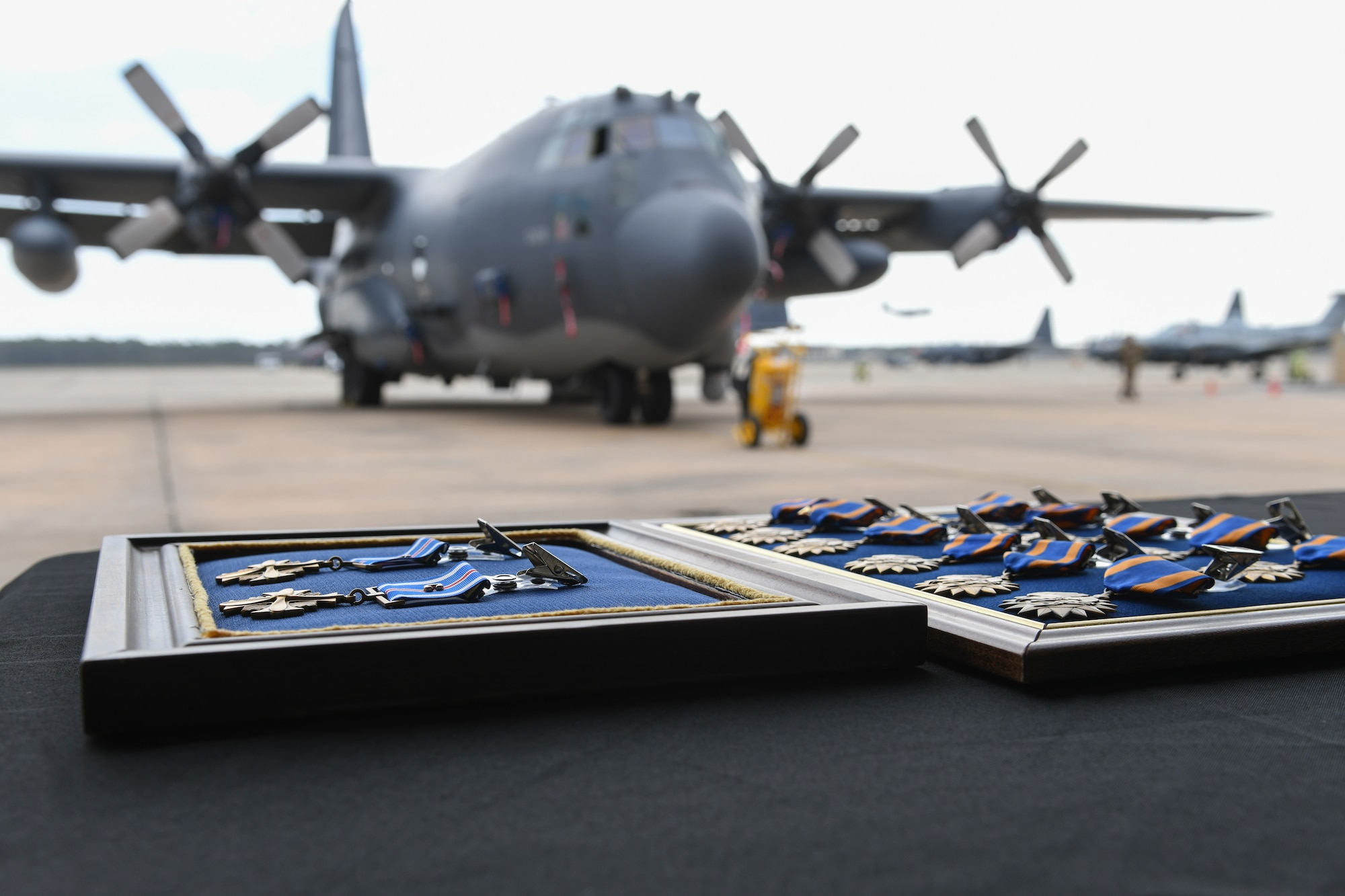 """Two Distinguished Flying Cross medals and 12 Air Medals lay on a table before a presentation ceremony at Hurlburt Field, Fla., March 2, 2020. During the ceremony, 14 air commandos with the 4th Special Operations Squadron were presented two DFCs and 12 Air Medals in recognition of actions taken near Nangarhar Province, Afghanistan, April 3-4, 2019, with the AC-130U """"Spooky"""" Gunship. During a nine-hour period, the crew's exemplary performance and battlefield coordination enabled the recovery of 15 patients following a mass-casualty event. (U.S. Air Force photo by Airman 1st Class Hailey M. Ziegler)"""