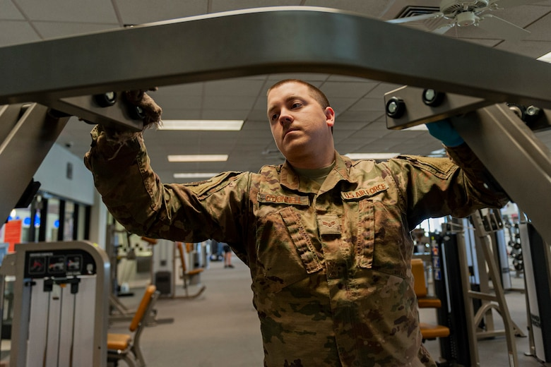 Photo of Airman cleaning fitness equipment