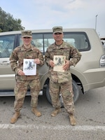 Chief Warrant Officer 2 Benjamin Brumfield, human resources systems division chief, 14th Human Resources Sustainment Center, 1st Theater Sustainment Command, and his son, Spc. Jonathan Brumfield, information technology specialist with Headquarters and Headquarters Battery, 1st Battalion, 7th Air Defense Artillery Regiment, 108th Air Defense Artillery Brigade, hold up their certificates upon completing the Norwegian Foot March at Camp Arifjan, Kuwait on Feb. 17, 2020. (Contributed)