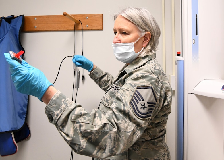 Master Sgt. Terrylee Crowther, 104th FW Dental Assistant puts on protective equipment for a dental examination. As the NCOIC of Dental at the 104th Fighter Wing, she ensures members are up to date on dental screenings so they can stay deployment ready. (U.S. Air National Guard Photo by Airman Camille Lienau)
