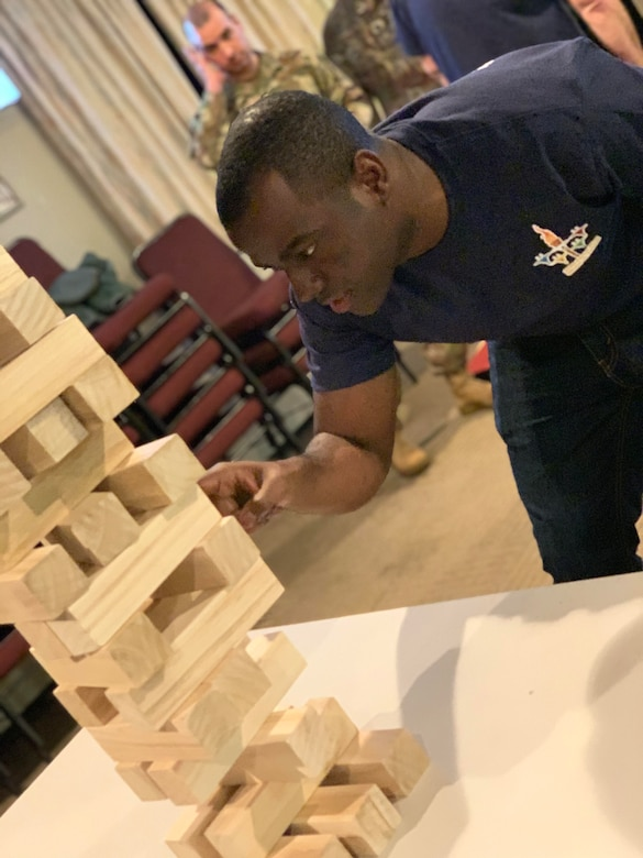 Staff Sgt. Shemron Ross of the 104th Force Support Squadron removes a game piece from the Jenga tower with intense concentration during the 104th Fighter Wing's 2nd annual Officer vs. Enlisted Olympic games, Feb. 1, 2020. The enlisted and the officers took part in a friendly competition as part of the Wing's camaraderie with the final score of enlisted 14 officers 13. (U.S. Air National Guard photo by Senior Master Sgt. Julie Avey)