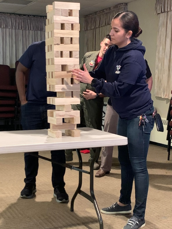 Airman 1st Class Mabell Teixeira of the 104th Force Support Squadron removes a game piece from the Jenga tower with intense concentration during the last competition against the officers. At the same time, the officers strategize their next move during the 104th Fighter Wing's 2nd annual Officer vs. Enlisted Olympic games, Feb. 1, 2020. The enlisted and the officers took part in a friendly competition as part of the Wing's camaraderie with the final score of enlisted 14 officers 13. (U.S. Air National Guard photo by Senior Master Sgt. Julie Avey)