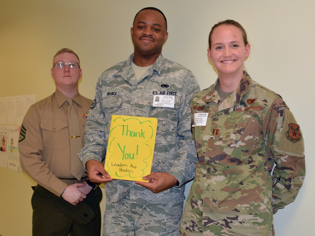 DLA Aviation military members pose with thanks you card given to them by elementary school students