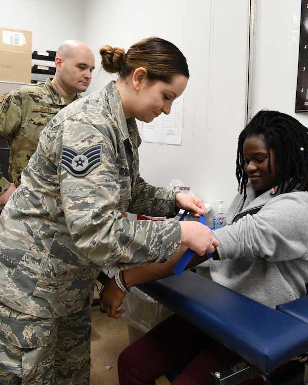 Chief Master Sgt. Jim Brown, 104th Medical Group Superintendent, works with Staff Sgt. Olivia Briggs, 104 MDG apprentice, to provide medical care. The 104th Medical Group recently got new AFSCs which will give them the opportunity to provide more focused care to Airmen.  (U.S. Air National Guard photo by Airman 1st Class Sara Kolinski)
