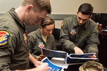 Three Airmen review tactical strategies on paper.