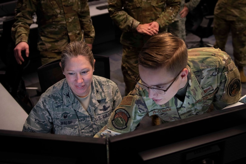A young airman points to an image on a computer screen.