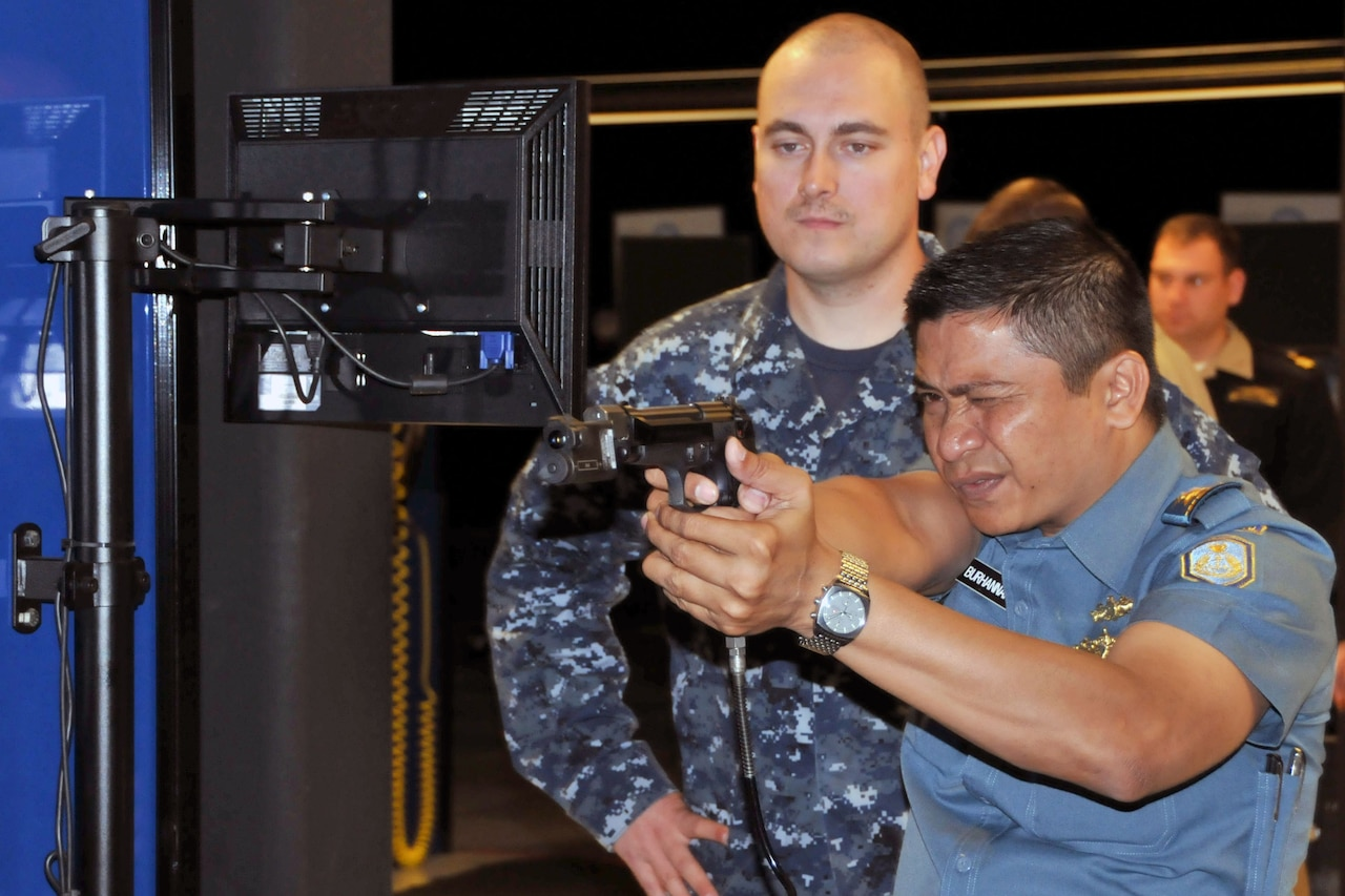 A foreign service member aims a pistol while another watches.