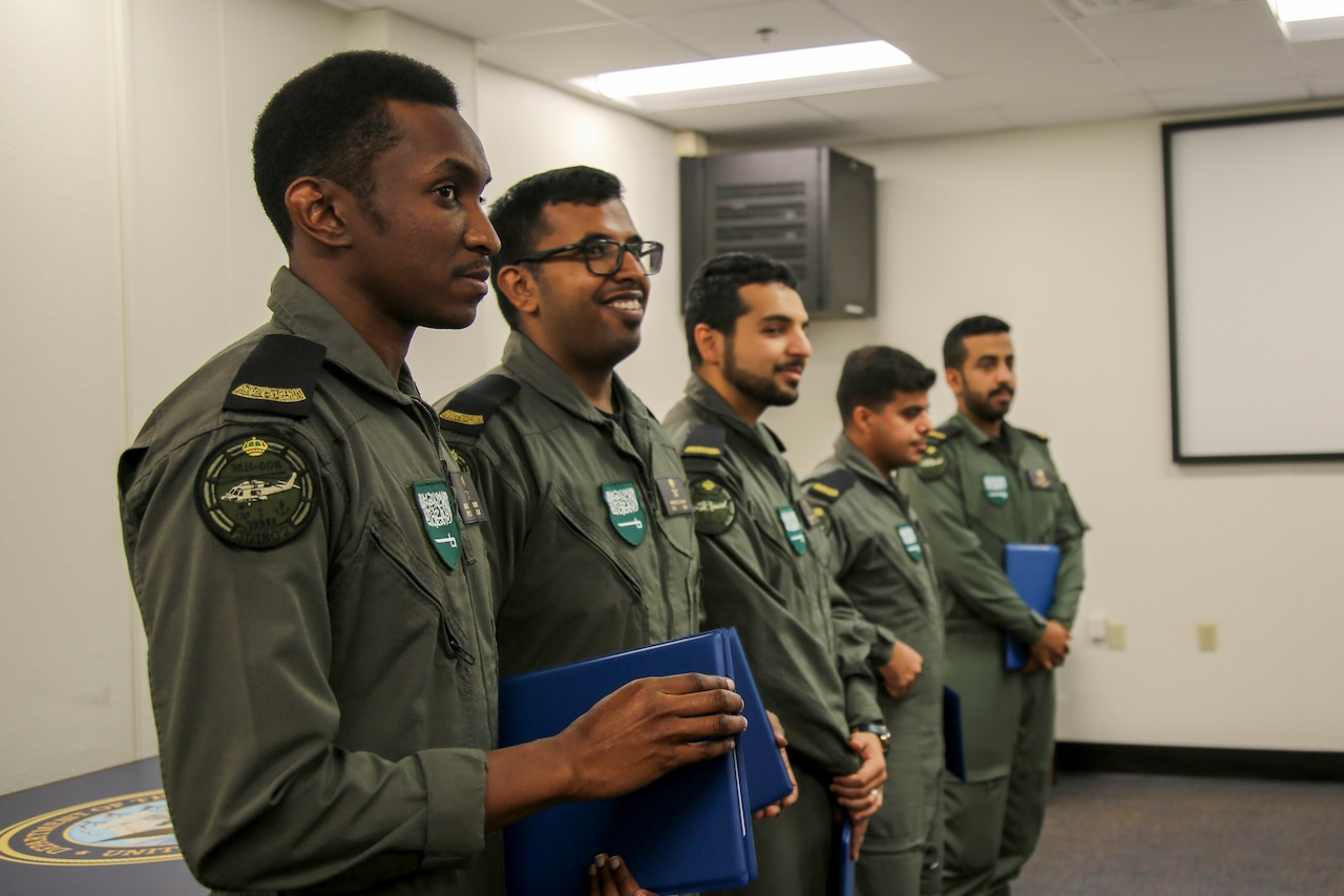 Five military service members stand in a line; each holds a blue folder.