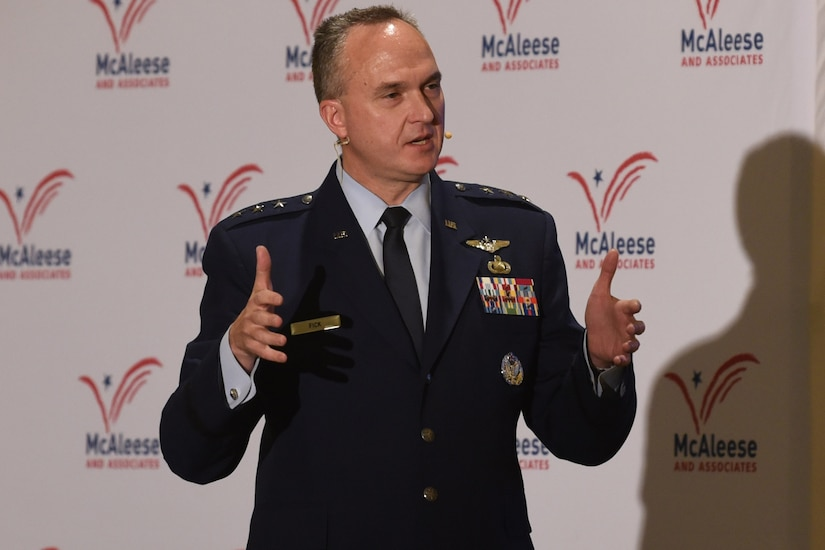 A man in a military uniform speaks into a microphone on a headset.