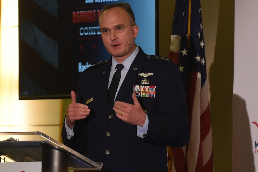 A man in a military uniform speaks from behind a podium.