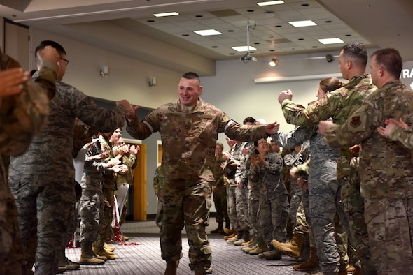 U.S. Air Force Senior Master Sgt. select John Brahm, 17th Communications Squadron flight chief, runs through an aisle of supporters, coworkers and family during the Senior Master Sgt. release party at the event center on Goodfellow Air Force Base, Texas, March 3, 2020. The aisle allowed everyone to fist bump and high-five the selectees before they received their certificates. (U.S. Air Force photo by Senior Airman Seraiah Wolf)