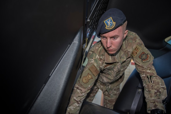 U.S. Air Force Senior Airman Anthony Meinert, 60th Security Forces Squadron installation entry controller, inspects a vehicle March 3, 2020, at Travis Air Force Base, California. Meinert was the Warrior of the Week from March 1-7. The program recognizes Airmen who have made significant contributions to their units. (U.S. Air Force photo by Airman 1st Class Cameron Otte)