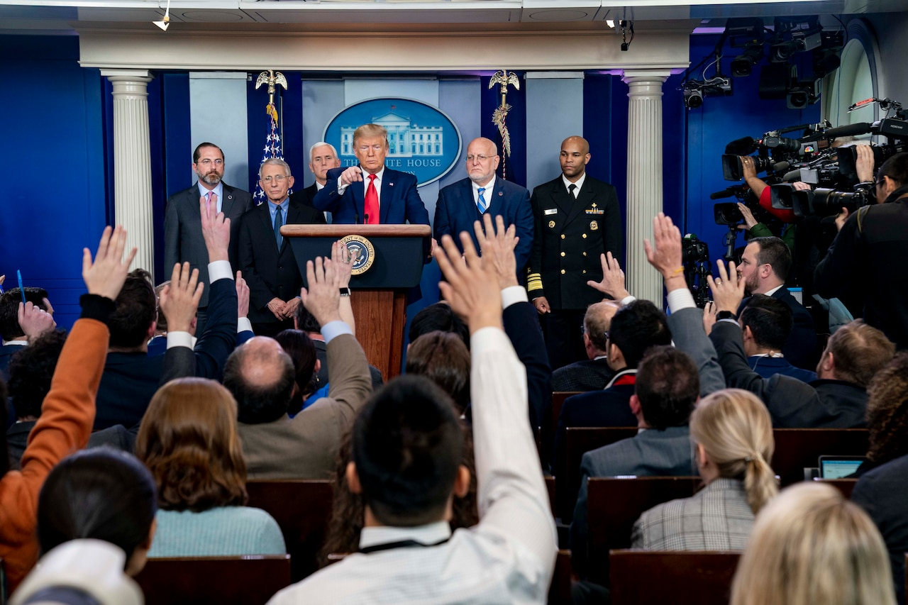 Men and women raise their hands as a man standing at a lectern points to one.