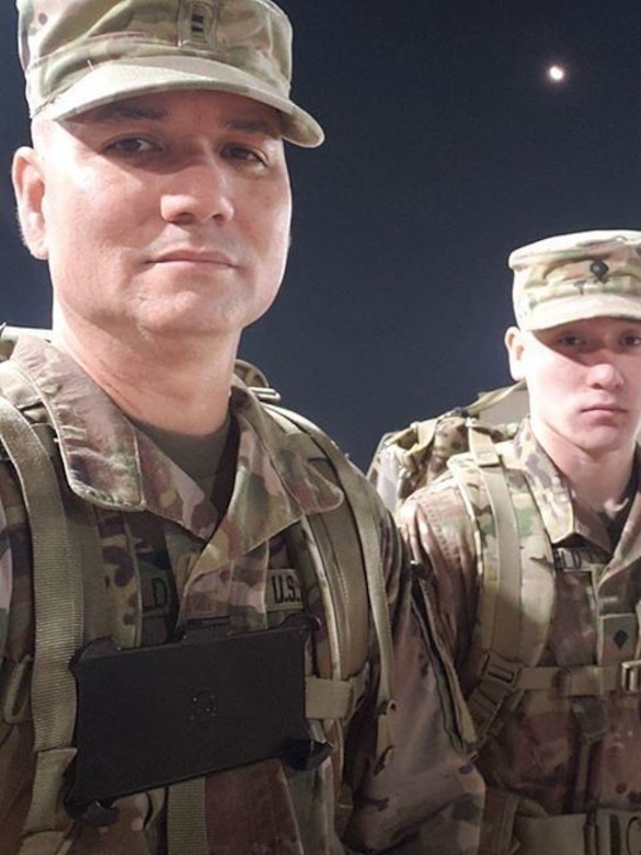 Chief Warrant Officer 2 Benjamin Brumfield, human resources systems division chief, 14th Human Resources Sustainment Center, 1st TSC, and his son, Spc. Jonathan Brumfield, information technology specialist with Headquarters and Headquarters Battery, 1st Battalion, 7th Air Defense Artillery Regiment, 108th Air Defense Artillery Brigade, wear their 25-pound rucksacks during the Norwegian Foot March Feb.17, 2020 at Camp Arifjan. (Contributed)