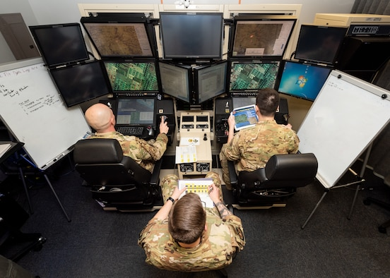A pilot, sensor operator and an additional airman sit at an MQ-9 Reaper flight simulator.
