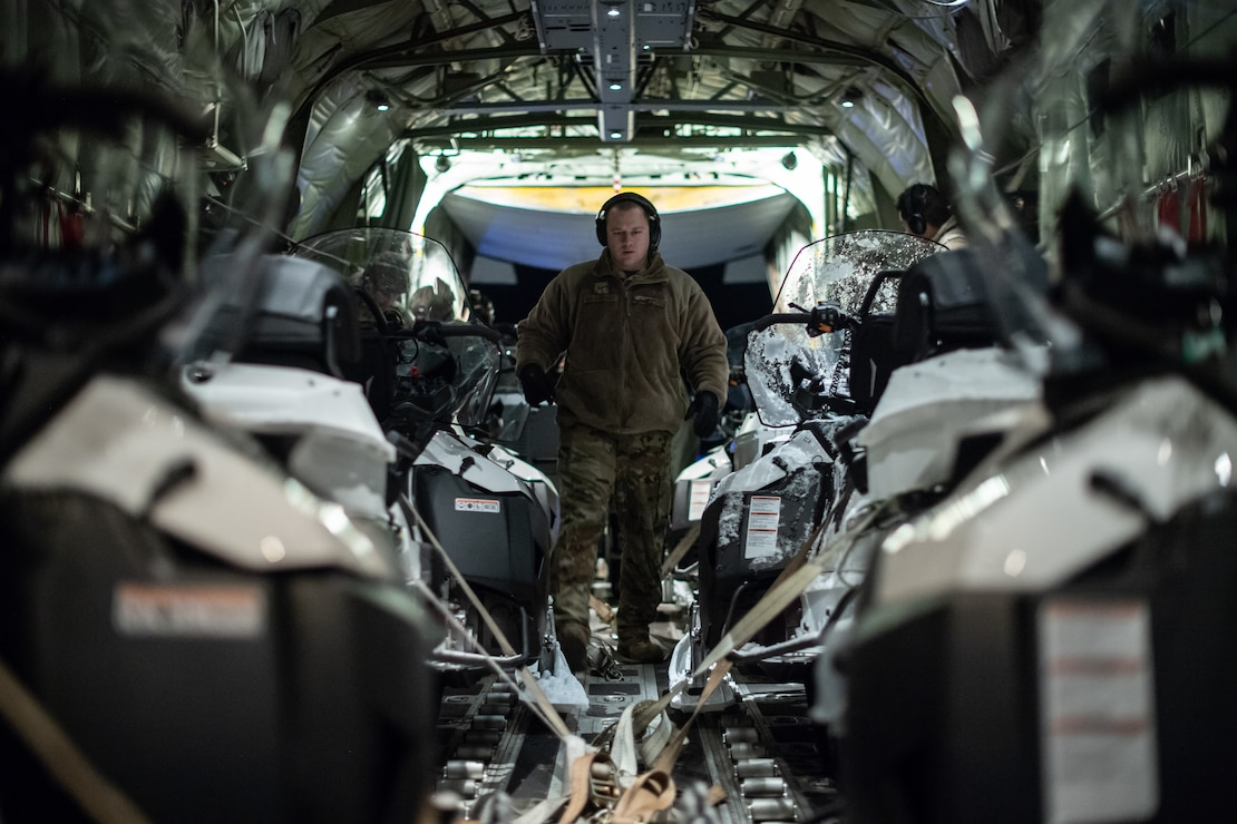 U.S. Air Force flying crew chief navigates through snowmobiles aboard a C-130J Super Hercules at an airport in Kiruna, Sweden, prior to Exercise Cold Response 20, Feb. 27.