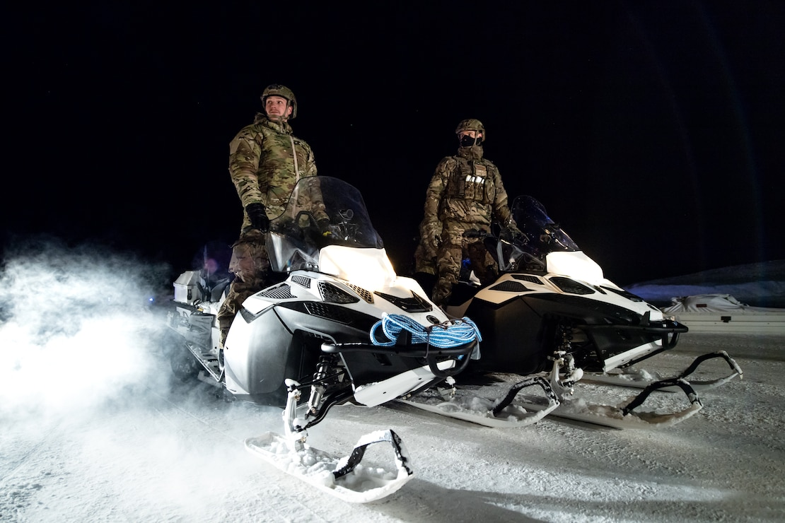 British Royal Marines Commandos prepare to load snowmobiles onto a C-130J Super Hercules at an airport in Bardufoss, Norway, prior to Exercise Cold Response 20.