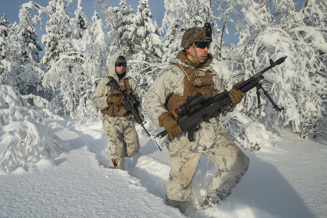 U.S. Marines rush through the tree line during exercise Snow Panzer in Setermoen, Norway, Feb. 25.