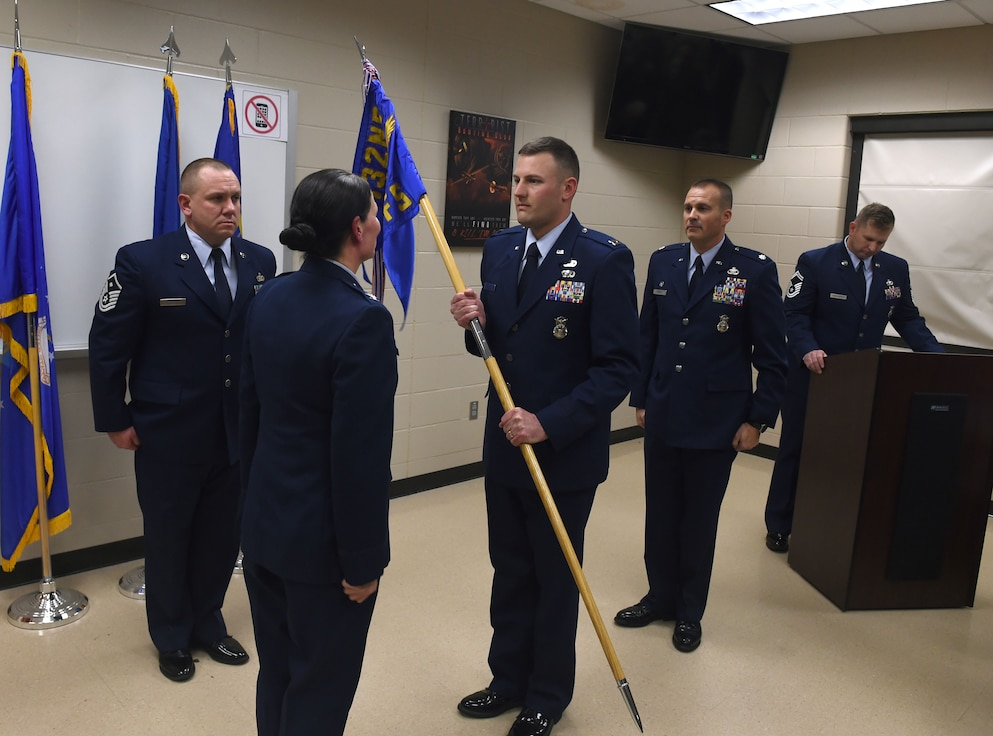 Capt. Adam Christian (holding flag) assumes command of the 132d Security Forces Squadron, February 1, 2020 at the 132d Wing in Des Moines, Iowa. Christian holds the commander position as a traditional Guardsman. (U.S. Air National Guard photo by Staff Sgt. Michael J. Kelly)